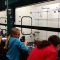 3 Girl scouts using science equipment